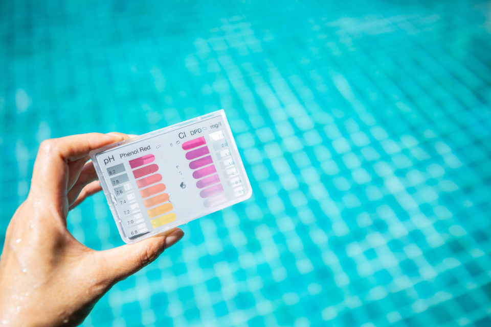 Holding a chlorine test over a swimming pool