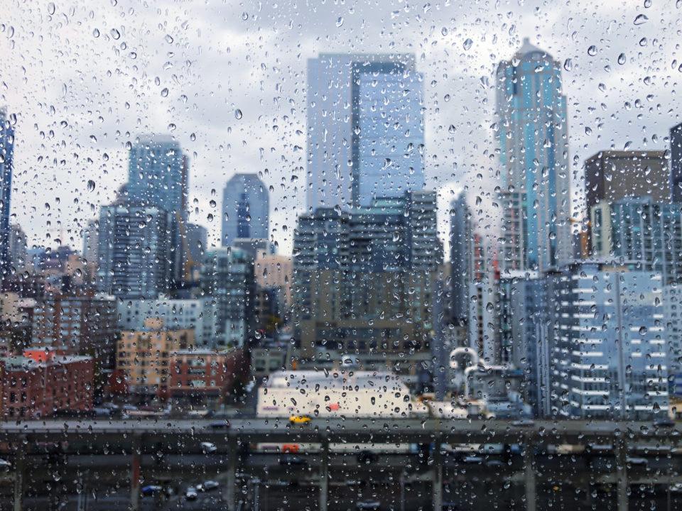 Cityscape seen through wet window during rain