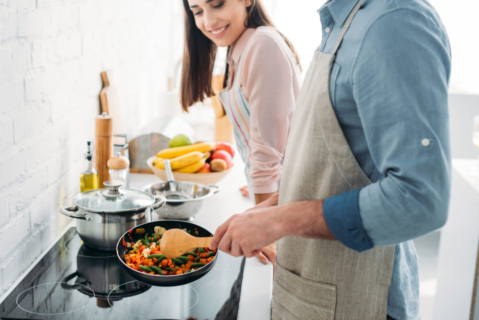 Couple cooking vegetables in their kitchen