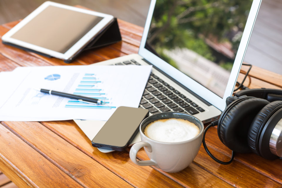 Desk with electronics, documents, and coffee - Sustainability Reporting Services