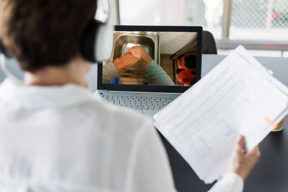 Man watching remote audit on laptop - Virtual Audits and Next-Gen Livestream Communications   NSF International