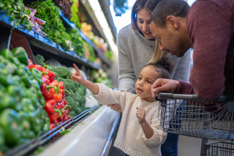 A young girl helps her parents pick out red peppers in the produce section at the grocery store.