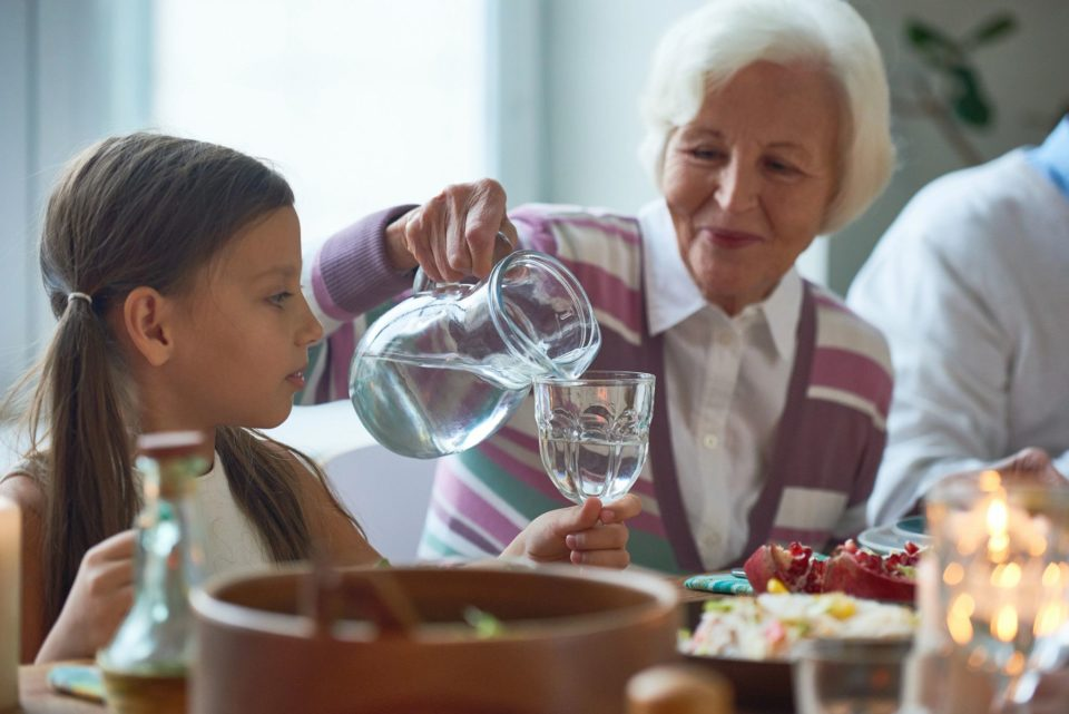 Grandmother pouring water for granddaughter at dinner table