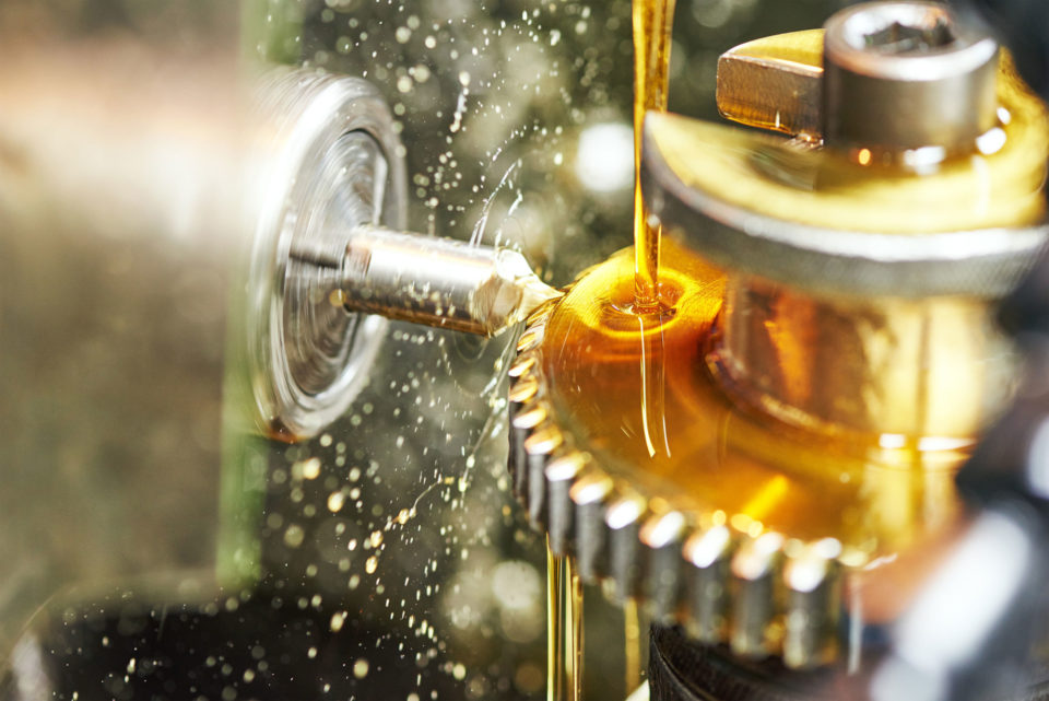 Machine with golden oil dripping onto gears