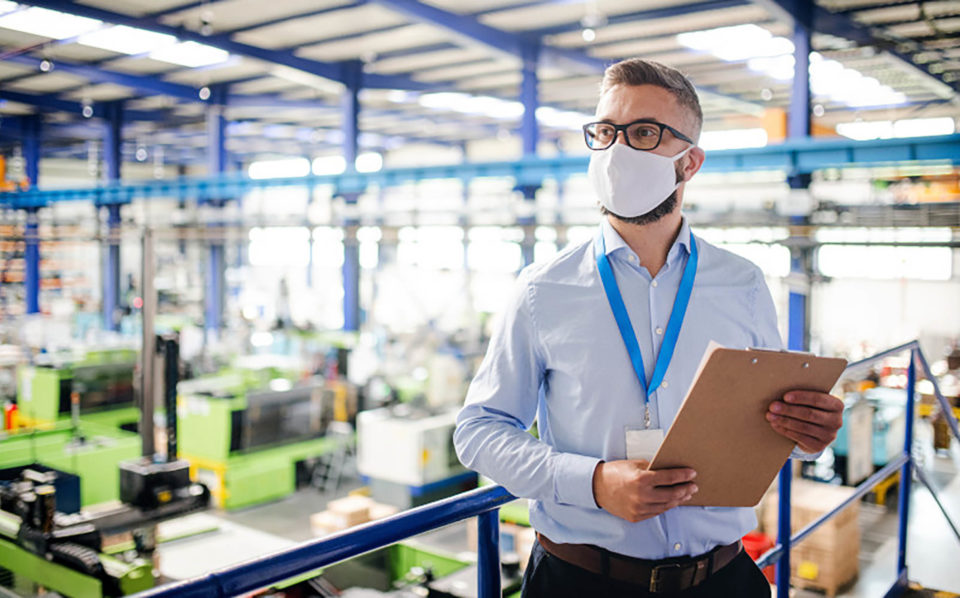 Man wearing mask and holding a clipboard while in factory