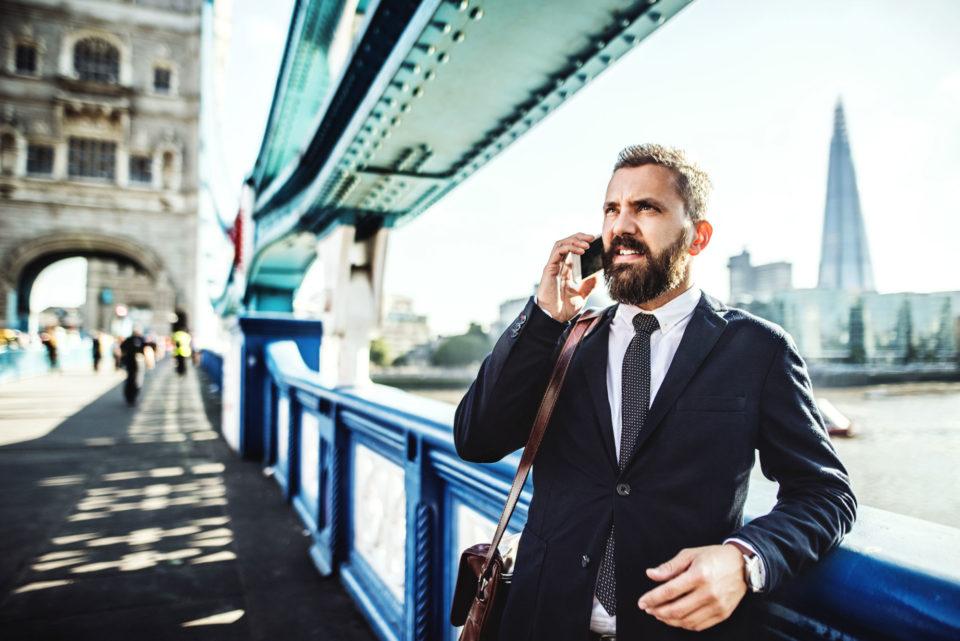 Man talking on cellphone under a bridge in London