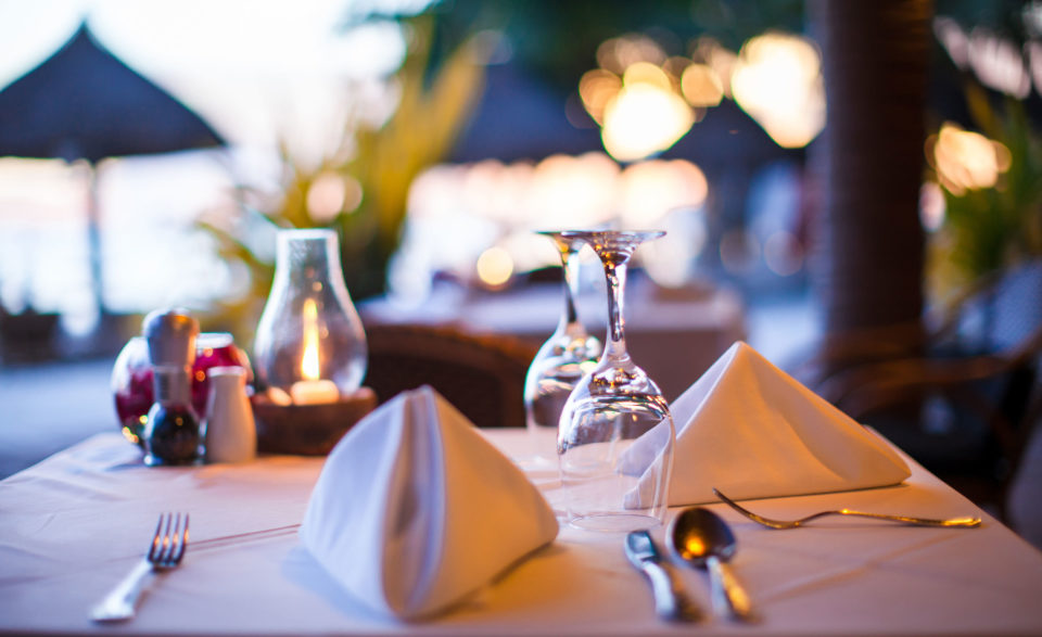Outdoor restaurant table setting at dusk with cloth napikins