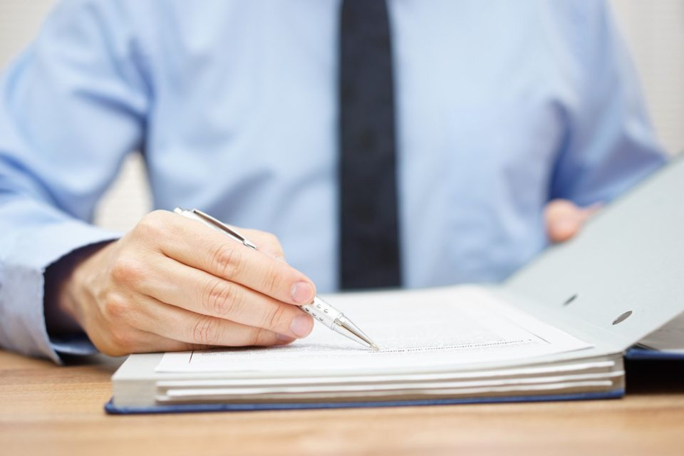 Man pointing pen at wording on paper