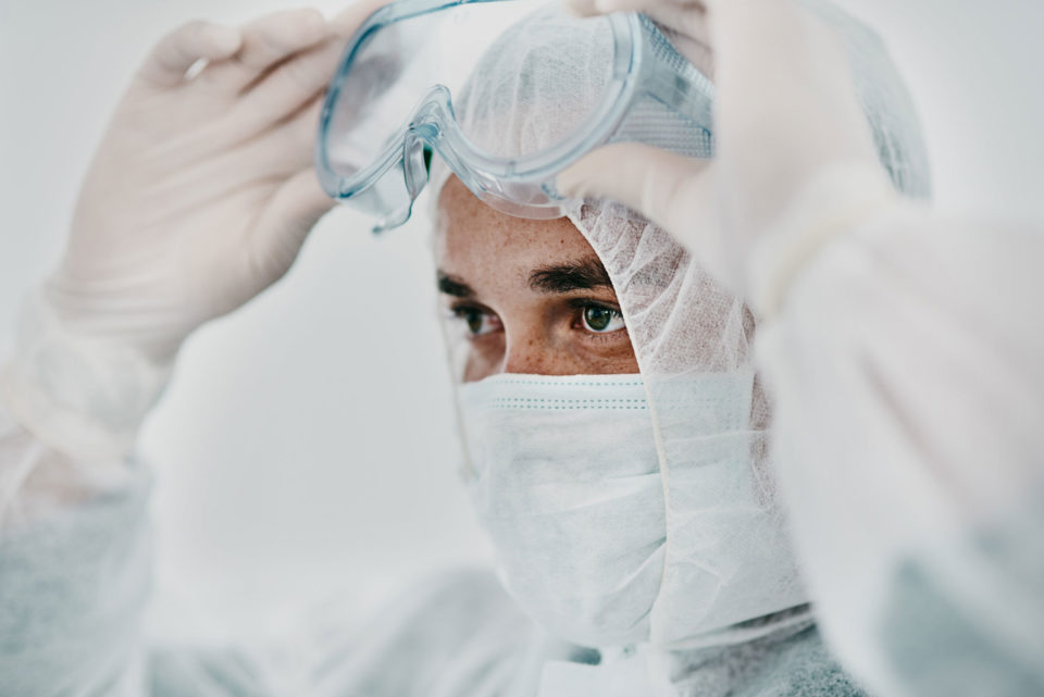 Shot of a young man putting on googles wearing protective gear