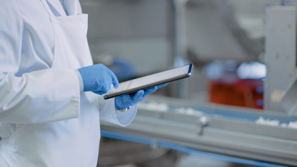 Production facility worker using tablet while wearing gloves – Region of Waterloo COVID-19 Safe Ambassador Program | NSF International
