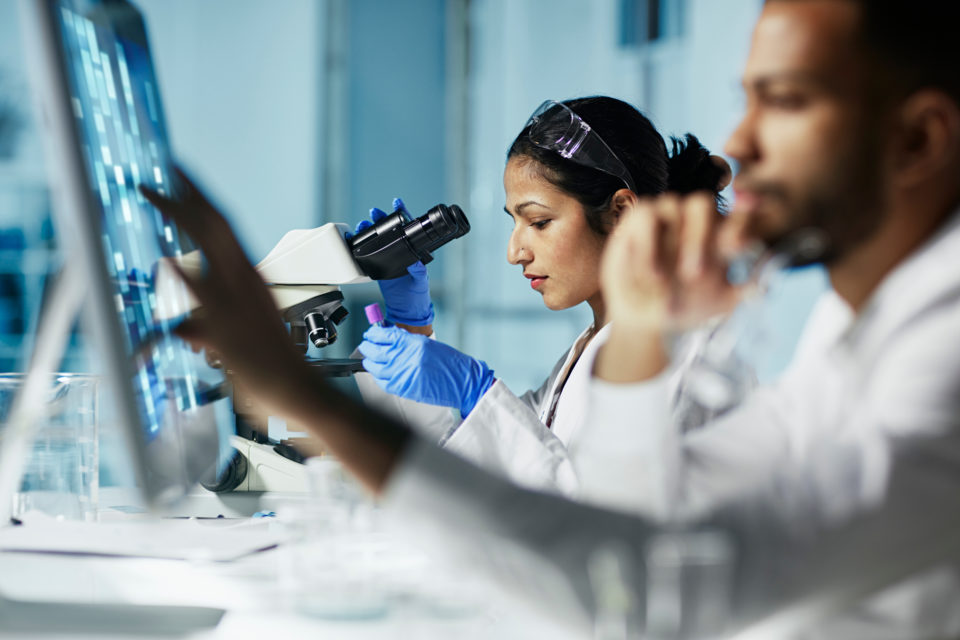 Scientists working on computer and microscope in laboratory