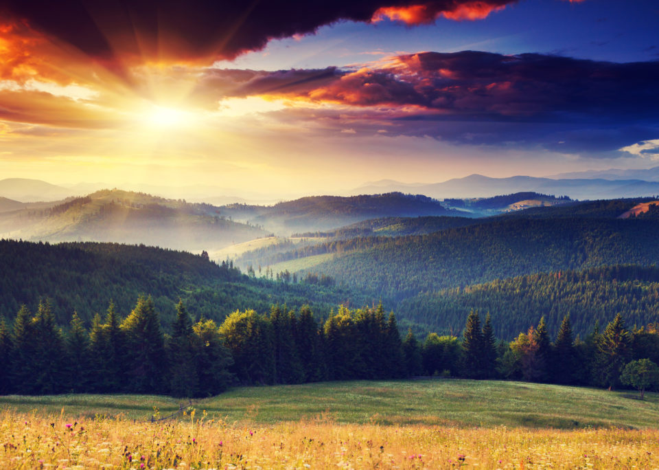 Sun over mountains and fields