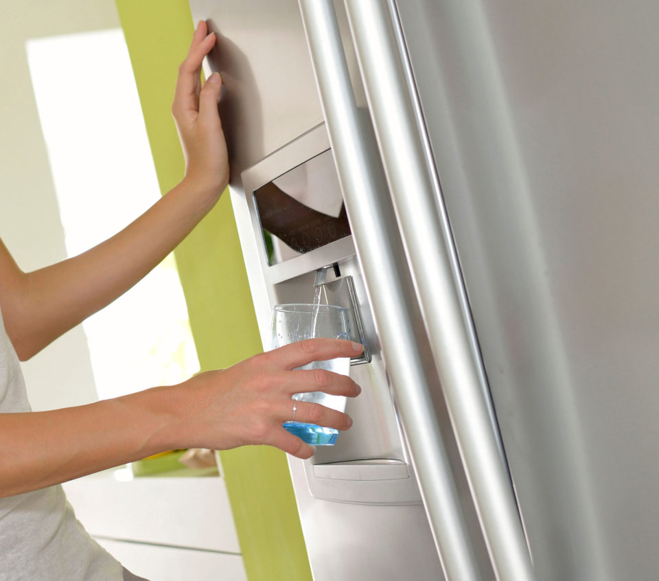 Woman getting water from a fridge dispenser