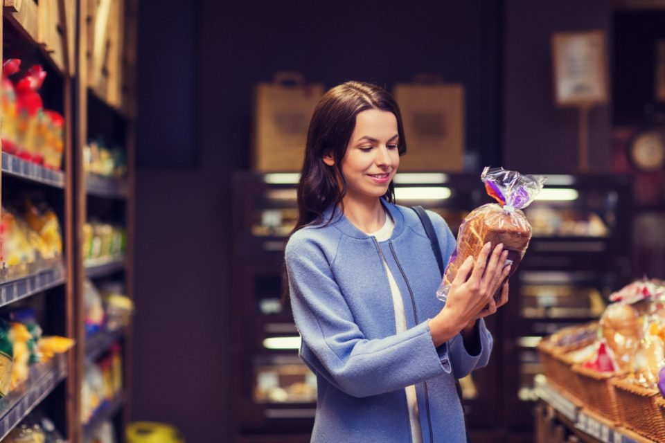 Woman selecting commercially packaged bread at a supermarket
