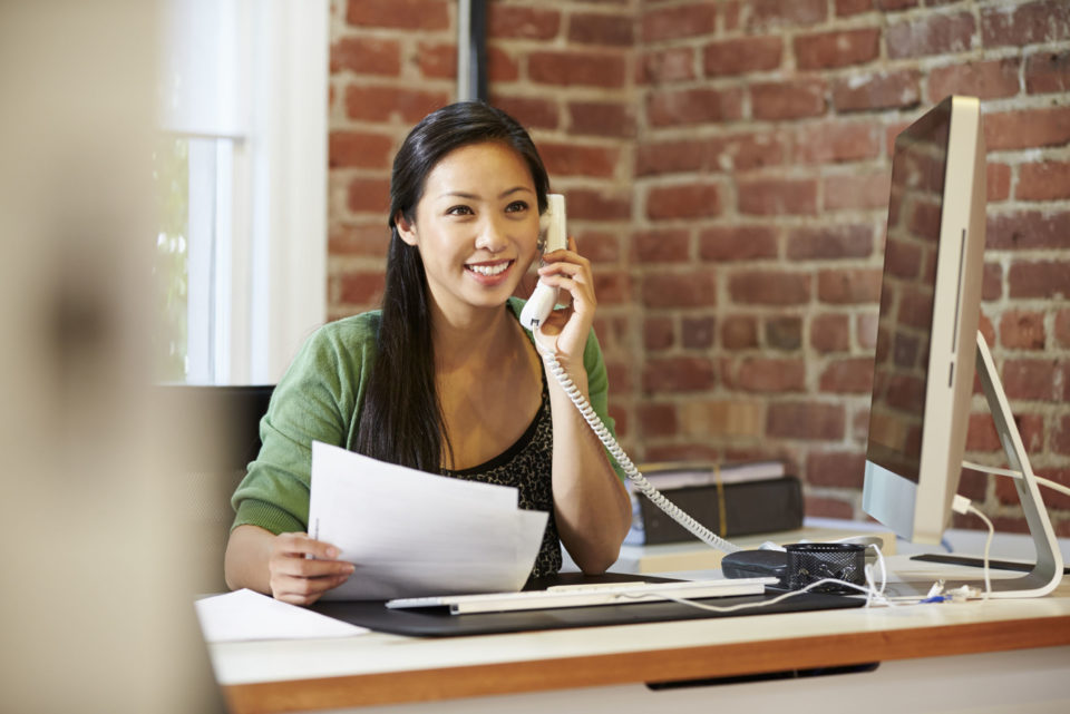 Woman sitting at desk while on the phone and holding papers