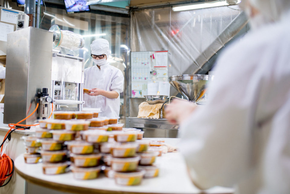 Workers in a food processing factory packaging food - Nonfood Compounds and Chemical Registration